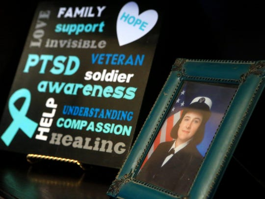 A photo of Navy veteran LeeAnn Fox is displayed with artwork she created. Fox said she felt out of sync and alone when she retired from the military.