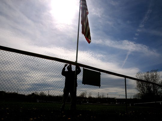 Chris Ruggieri, head baseball coach at Greece Arcadia, raising the flag at the centerfield fence before a game.