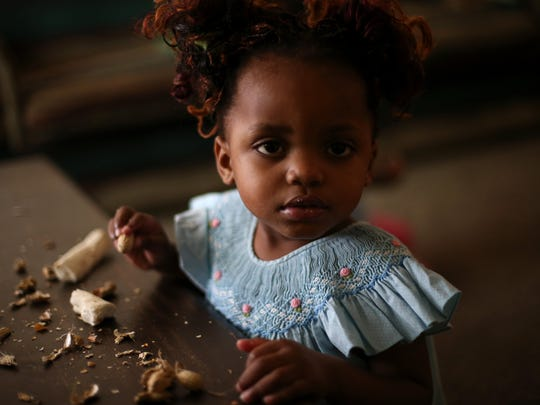 Madede Mambo, 2, eats Cassava root in the family's living room in Tallahassee.