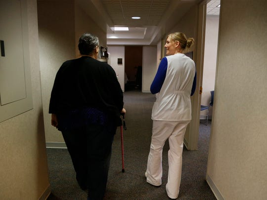 Karen Slessor of Reinbeck, Iowa (left, walks with regisered nurse Lacy Kolder Wednesday, May 3, 2017 during an appointment at Wolfe Eye Clinic in Cedar Falls, Iowa.