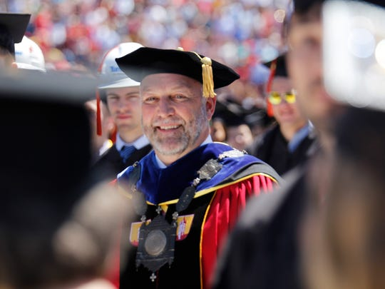 Former Iowa State University President Steven Leath approaches the stage after he was introduced at the 2017 graduation ceremony.
