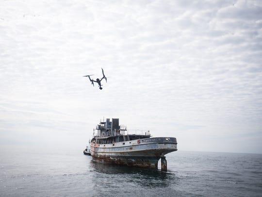 A drone takes off to survey the Tamaroa as crews work