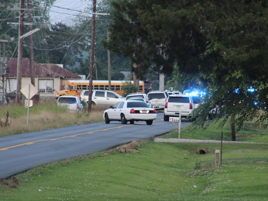 Dozens of vehicles from Louisiana State Police and other law enforcement agencies sit stationed around a home on La. Highway 114 in the Long Bridge community Thursday. A man who was barricaded inside a home after a police chase shot at least one trooper before he later was taken into custody.