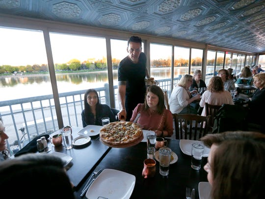 Server Henry Avignon brings a Massimo pizza to the table during the second stop, for entrees, at Tony D's in Corn Hill Landing.