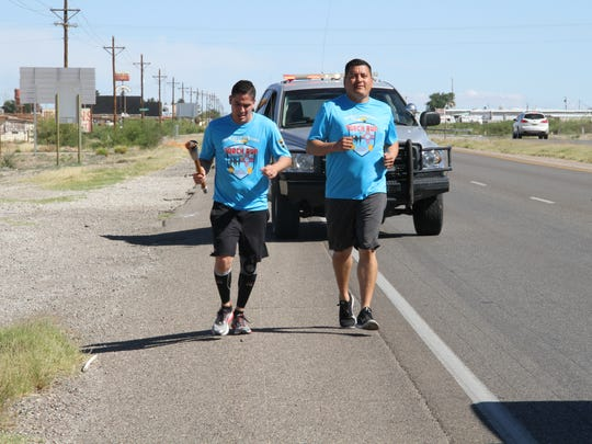 Otero County Sheriff's Office detective Sam Montoya (L) and OCSO deputy Raul Robles run with the Special Olympics torch along U.S. Highway 54 to bring awareness to children with special needs May 12.