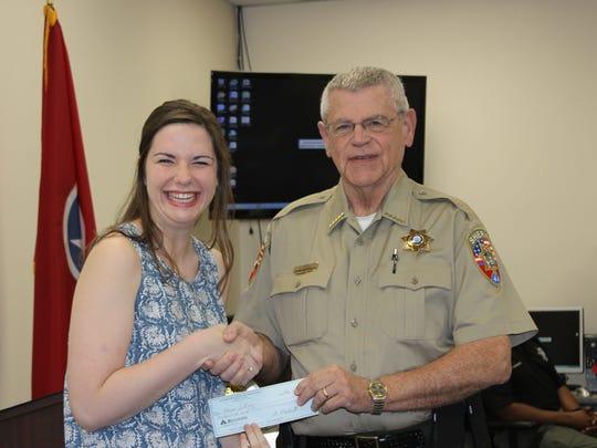Central Magnet senior Morgan Sullivan receives a $1,000 SRO scholarship from Sheriff Mike Fitzhugh.