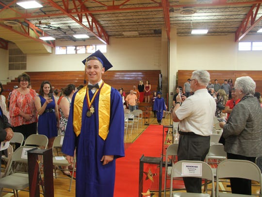 Valedictorian Nathan Brown walks to his seat at the