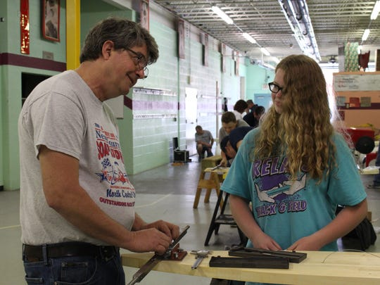 """Derby dad"" John Fort helps first-time race Abbie Durbin of Plymouth work on her car during Builder's Day on Sunday, May 21, 2017. Durbin's grandfather also helped her with her car ahead of the North Central Ohio Soap Box Derby in June."