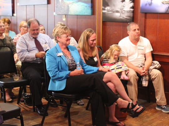 Rich Willett's family (first row) react as he reads a passage from his book.