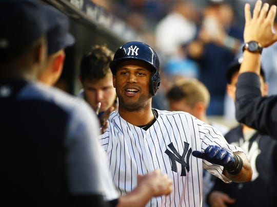 Yankees left fielder Aaron Hicks is congratulated in the dugout after hitting a solo home run against the Kansas City Royals during the fourth inning at Yankee Stadium on Tuesday.