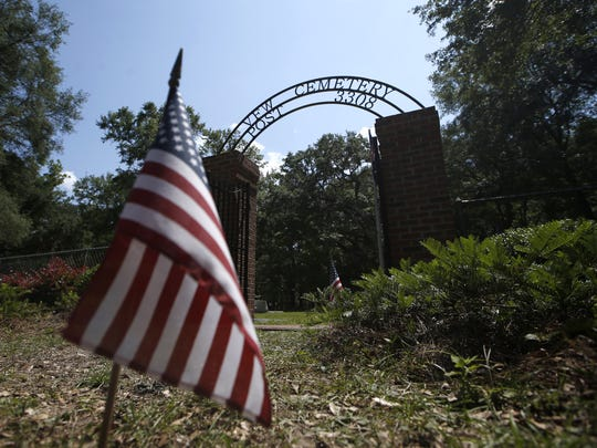 American flags are placed throughout the road leading to VFW Post 3308 Cemetery and among the graves during a ceremony on Memorial Day.