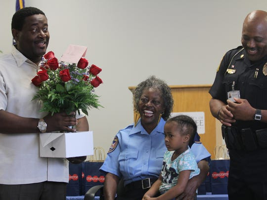 Rosa Flowers, center, retired after 28 years as a crossing guard Tuesday. Here her son gives her a bouquet of flowers as her granddaughter and TPD. Maj Roderick Young look on.