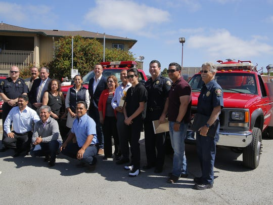 A mix of officials from the  cities of Salinas and Quiroga, Michoacan, Mexico pose for a photo with the two fire engines to be donated on Wednesday.