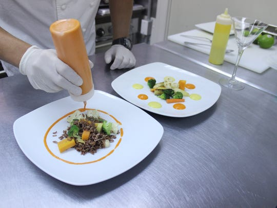 Shangri-La Springs Executive Chef Pyro Rodriguez plates two versions of his lionfish meal in the restaurant's kitchen.