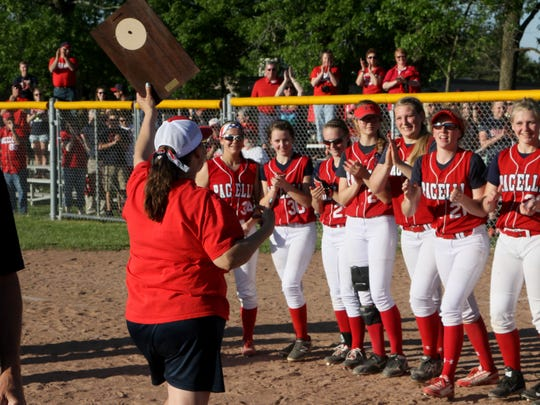 Pacelli softball coach Ann Molski holds up the WIAA Division 4 sectional championship plaque and prepares to celebrate with her players after an 8-6 win over Cochrane-Fountain City on Thursday at Tri-County High School.