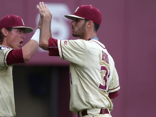 FSU's Tyler Holton, left, high-fives Alec Byrd as he comes off the mound againt Tennessee Tech during the Noles 5-3 Regional game win at Dick Howser on Sunday.