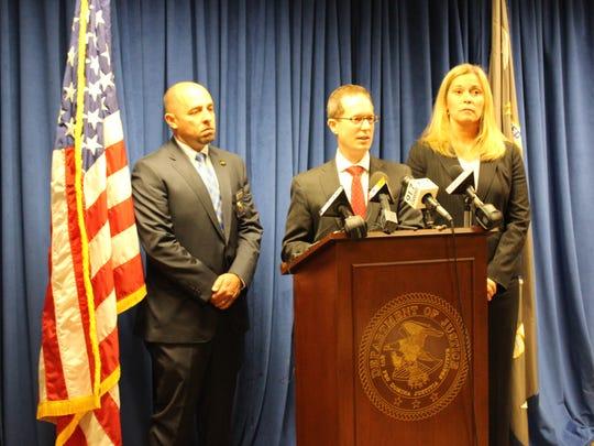 U.S. Attorney Benjamin C. Glassman, center, announced