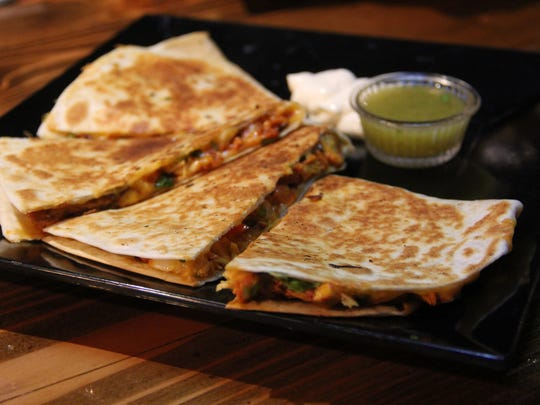 A quesadilla with chicken pairs diced vegetables with mild cheddar, served alongside a green tomatillo salsa.