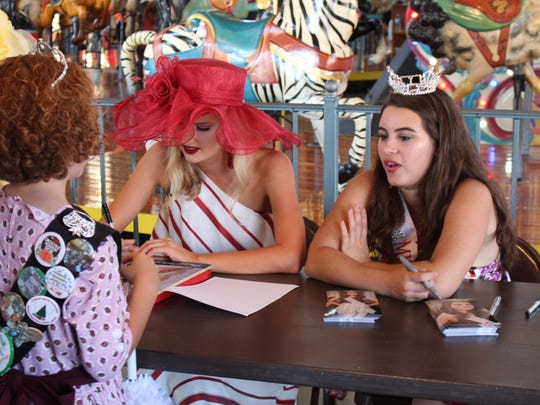 Miss North Coast Paige Wiers, in the red hat, signs an autograph for a fan at the Richland Carrousel Park after the Miss Ohio Parade. Wiers is one of 19 Miss Ohio contestants.