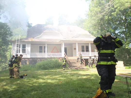 A firefighter begins the process of taking off his equipment after entering the burning home.