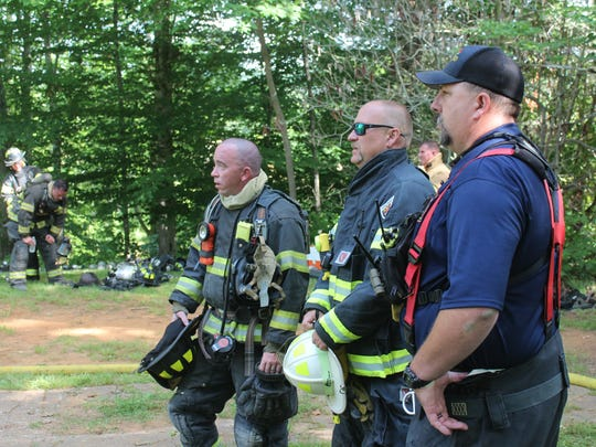 Joshua Norton of the Asheville and Hot Springs fire departments, watches the operation alongside Brian Hopps and Nathan Waldrup of the Mars Hill Fire Department.