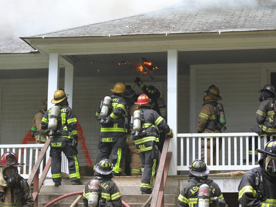 Firefighters use axes to cut holes in the roof of the porch.