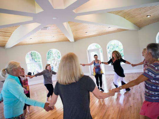 Instructor Valeria Hill, background right, in black and white outfit, dances and smiles while leading a Nia Dance class at Shangri-La Springs in Bonita Springs on Tuesday, May 9, 2017. Nia cardio-dance workouts combine 52 simple moves with dance arts, martial arts and healing arts.