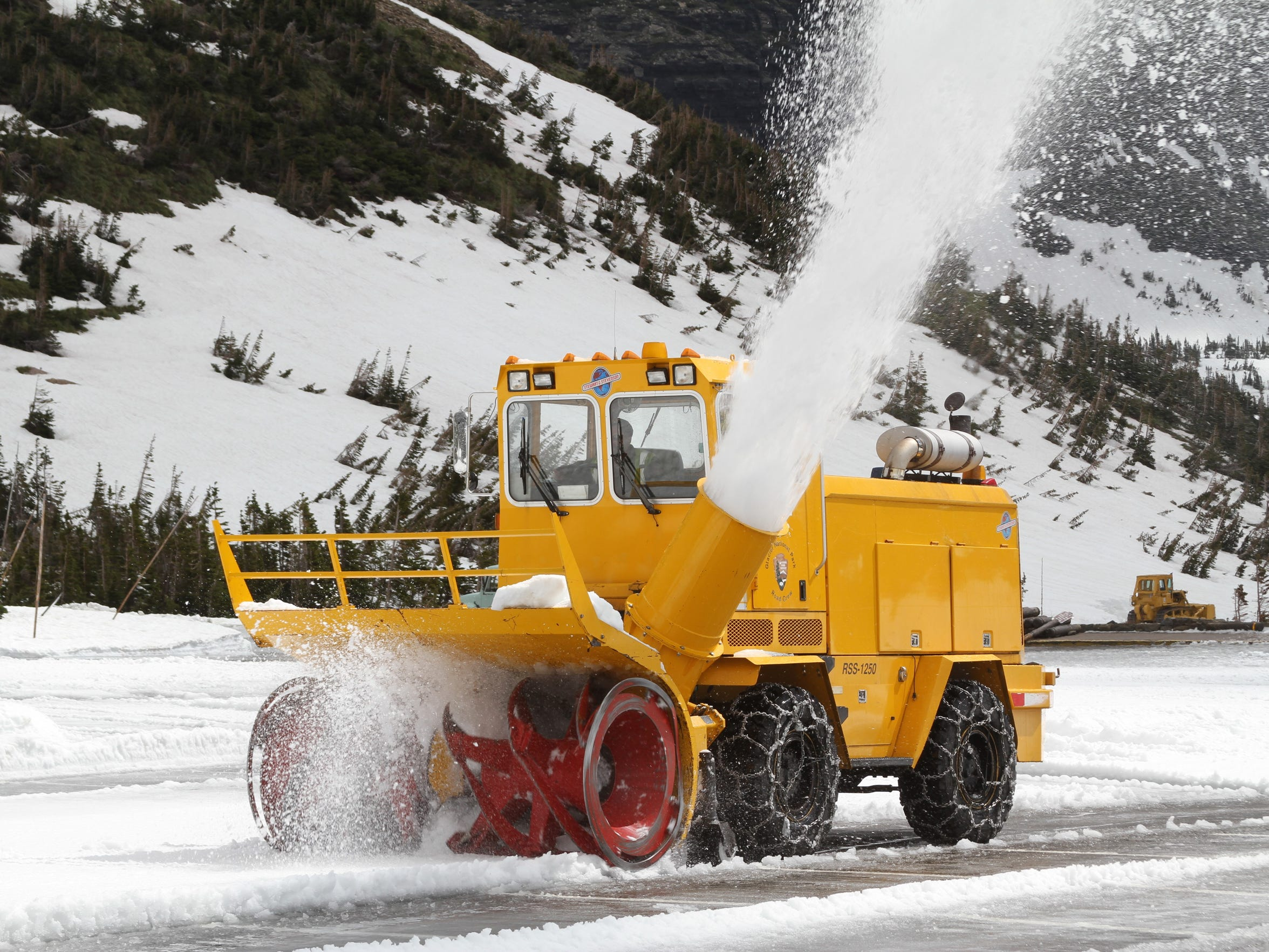 A rotary plow removes snow from the Logan Pass Visitor