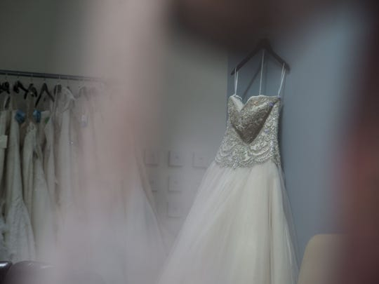 Pam Ronalter hangs a wedding dress in her boutique located on 5415 E High Street in Phoenix.