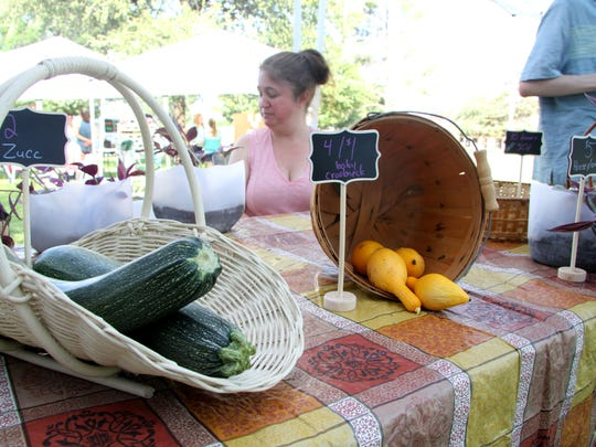 Stacey Blackmon sells zucchini and squash during the first day of the summer Carlsbad Farmers Market.