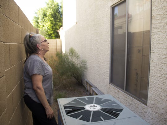 J. Lily Keohane, 64, next to her broken AC unit, examines