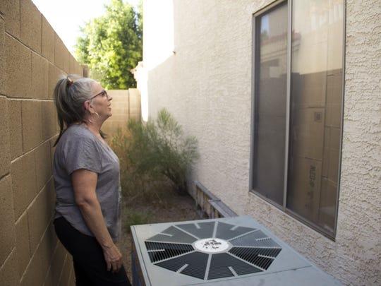 J. Lily Keohane, 64, next to her broken AC unit, examines