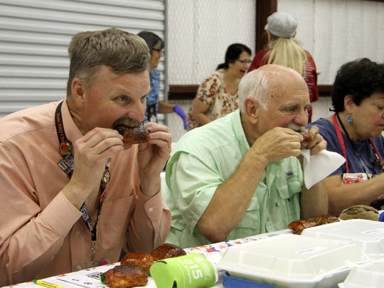 Judges taste barbecued chicken during Saturday's professional barbecue judging. They often take just one bite of each entry.