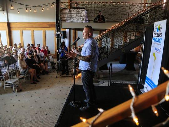 Artist Van Holmgren speaks during the Des Moines Storytellers