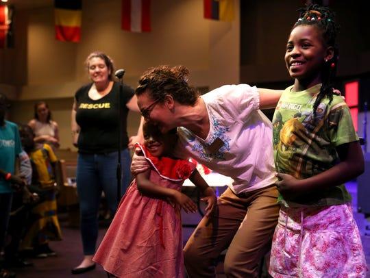 Kim Thacker shares an embrace with refugee children
