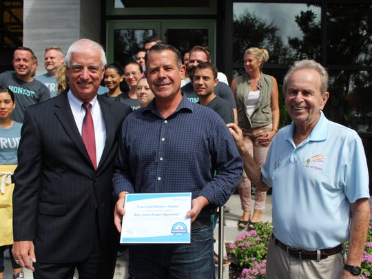 True Food Kitchen general manager Aaron Teegarden, celebrates Blue Zones approval with Naples Mayor Bill Barnett, right, and Mike Riley, chief strategy officer with the NCH Healthcare System, far left.