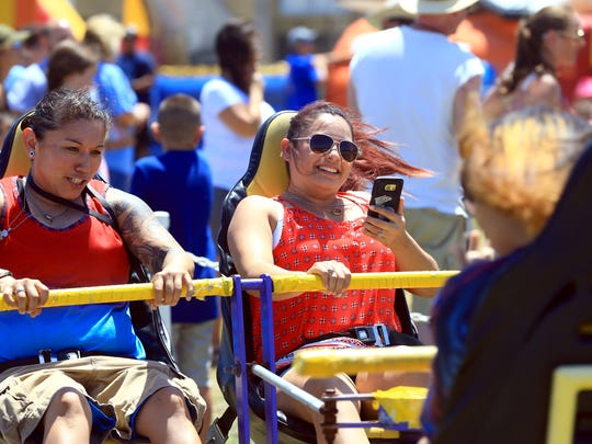 Brenda Alfaro (left) and Leslie Navarro hold on during a ride Tuesday, July 4, 2017, in the Kids/Game Zone at the Mayor's Fourth of July Big Bang Celebration in Corpus Christi.