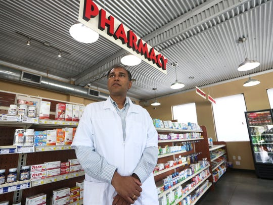 Harsh Patel stands in the aisle of his store, Care