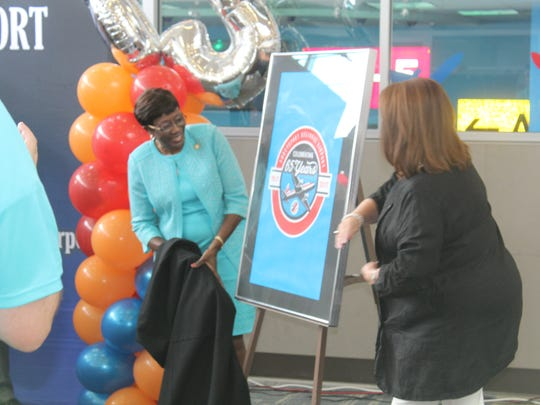 Shreveport Mayor Ollie Tyler and Margaret Shehee take the curtain off of a new logo commemorating the 65th anniversary of the Shreveport Regional Airport.