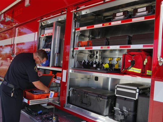 Salinas Fire Battalion Chief Chris Vaugn reviews the specialized equipment used for collecting and testing hazardous materials.