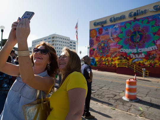 "Lisa Mills and Annette Medlin take a selfie in front of ""Endless Sunset: The Colors of Our City,"" a mural installation on the Caller-Times building following the dedication ceremony on Friday, Aug. 5, 2016."