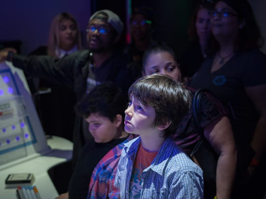 Young people try to discover clues and make their way through and out of Intergalactic Escape at the Franklin Institute.