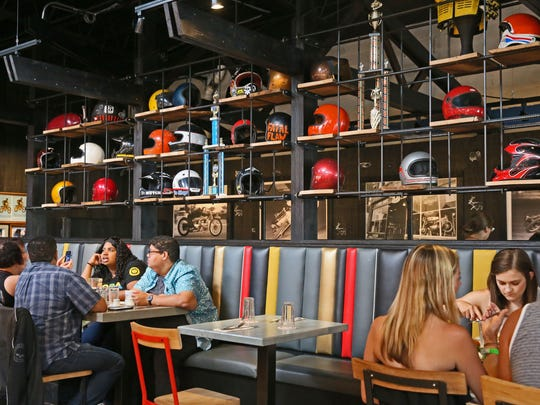 A display of motorcycle helmets divides the dining