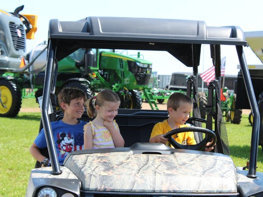 "Isaac Schneider's siblings Micah (left) and Annaleigh share his excitement during the ""Random Act of Light"" event at Farm Technology Days."