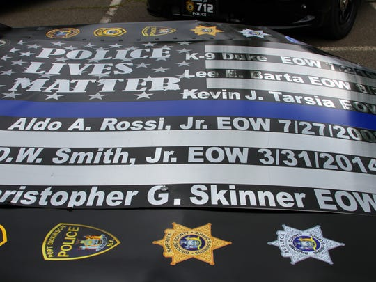 The race car features the names of local fallen police