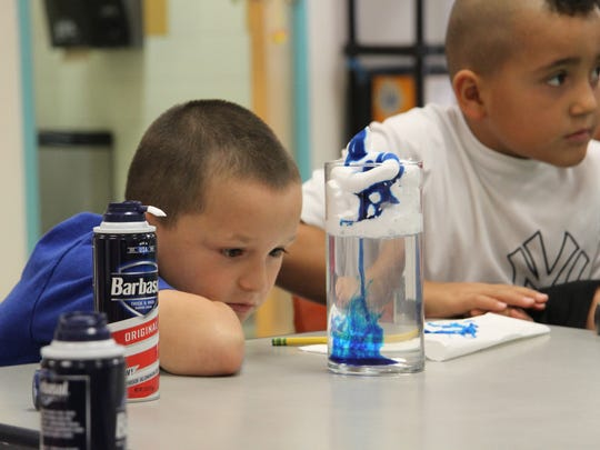 Second grader Javane Torres watches color dye mix with the water of cloud making experiment. The project was to make clouds using water and shaving cream. Students are made slime on STEM Day, July 13, 2017.