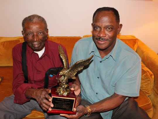 Herman Harris, left, and Montgomery Councilman David Burkette admire a small eagle statue presented to Harris on his 90th birthday.
