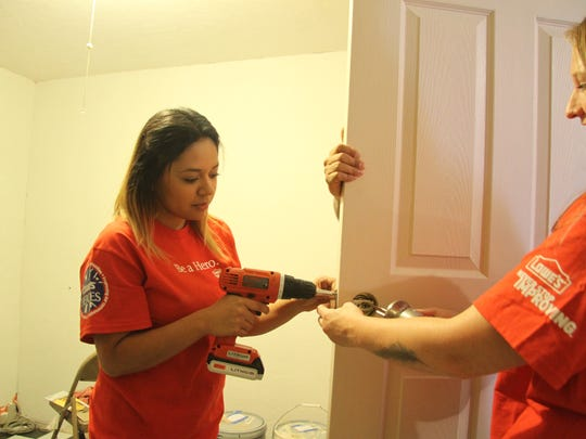 Lowe's project specialist Lupita Zacarias screw in the door handle at the new CASA building, July 14, 2017. Lowe's Home Improvement in Carlsbad renovated the new building in Artesia as part of the Lowe's Heroes Project.