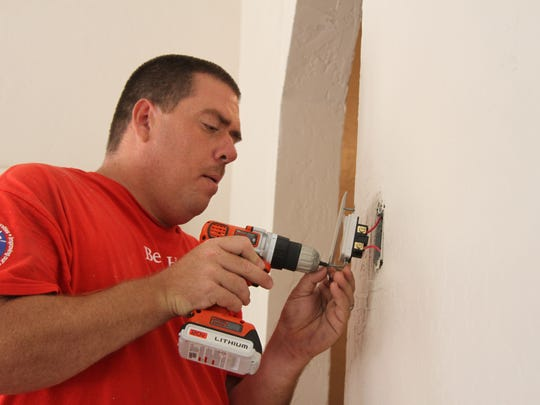 Lowe's assistant manager Patrick O'Brien works on the light switches at the new CASA building in Artesia, July 14, 2017.