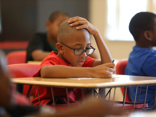 Ali Shabazz, 7, ponders over a nutrition facts worksheet as kindergarten through second grade students gather at FAMU DRS High School Wednesday for a six-week course created by the North Florida Freedom Schools.